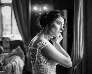 Bride putting on jewellery at Hengrave Hall