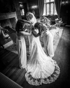 Bridesmaids attend to the bride at a Hengrave Hall wedding